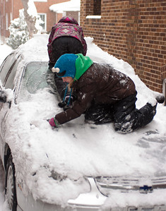 girls-on-car-hood-cleaning-snow